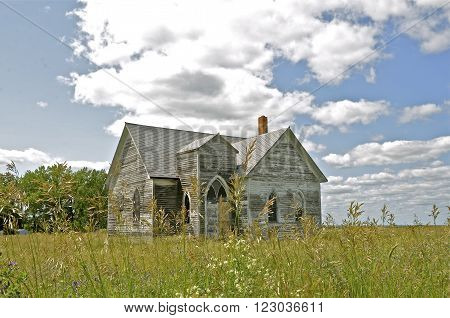 An old white church in the prairie grass stands abandoned, forlorn and displaying signs of neglect.