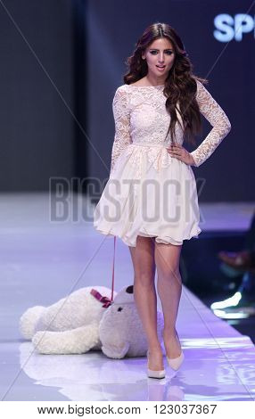 Sofia Bulgaria - March 23 2016: A model walks the runway with a Teddy bear at Sofia Fashion Week runway show. The fashion show is held for a second time in Bulgaria's capital.
