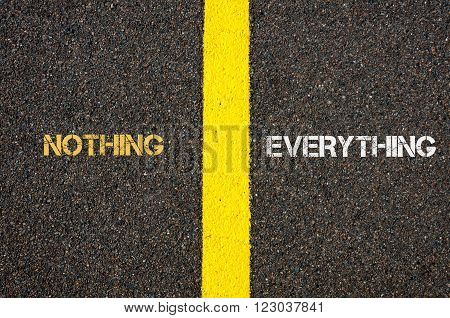 Antonym concept of NOTHING versus EVERYTHING written over tarmac, road marking yellow paint separating line between words