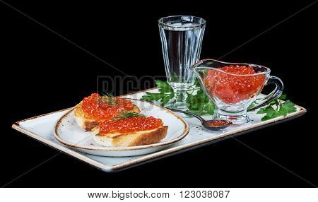 Sandwiches with fish eggs and glass of vodka on a porcelain plate isolated on black background