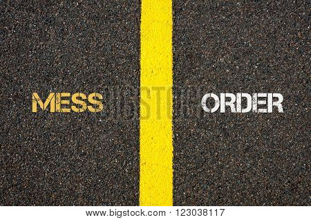 Antonym concept of MESS versus ORDER written over tarmac, road marking yellow paint separating line between words