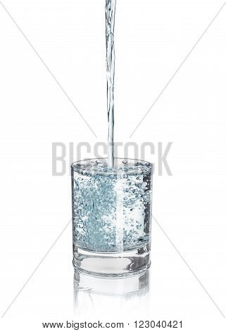 pouring water into the glass to the upside on an isolated white background