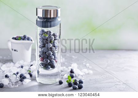 Infused water with mint and blueberries in a bottle
