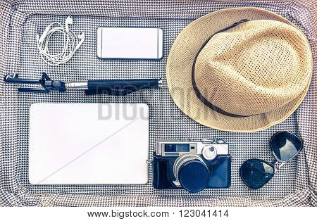 Traveler outfit and accessories for photographer - Overhead of essentials for modern young hipster - Travel and trend concept on retro suitcase - Soft green warm vintage filtered look