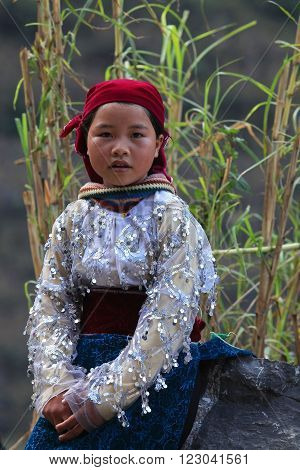 HA GIANG, VIETNAM - FEB 7, 2014: Portrait of an unidentified Hmong girl sitting on a stone on the side of mountain road.