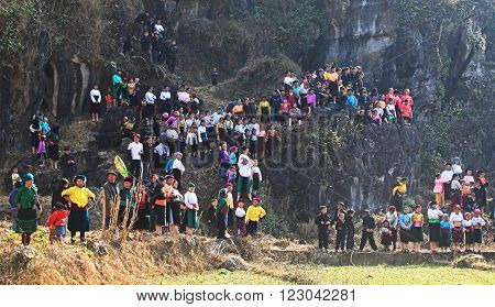 HA GIANG, VIETNAM - FEB 7, 2014: A group of unidentified Hmong women and children watching a traditional performance within a holiday called Tet under the sunlight of spring.