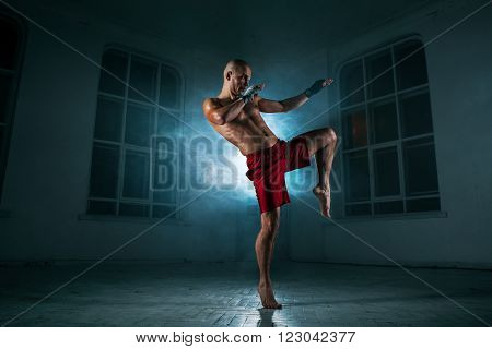 The young male athlete kickboxing on a background of blue smoke