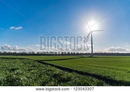 Wind turbine depicting the summit of green energy with wind and sun at highest point of the wind mill