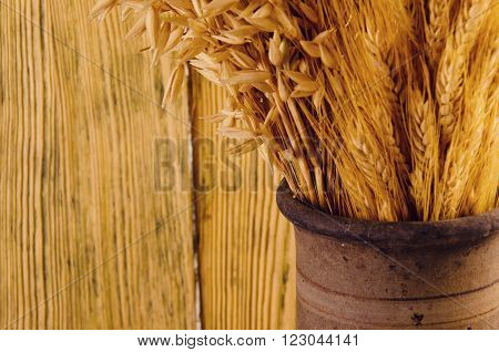 Old crock with a bunch of golden wheat ears against the background of a wooden wall (selective focus, with copy space for your text), retro style