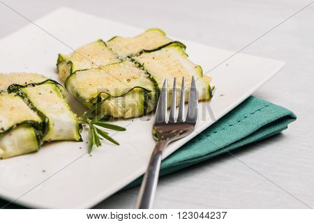Interlaced courgettes or zucchini slices and meat with grated cheese ready to be eaten
