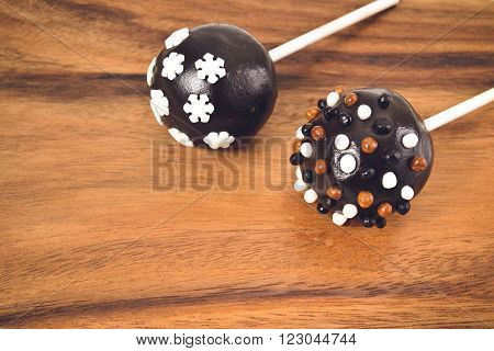 Delicious dessert - chocolate cakepops on a wooden background