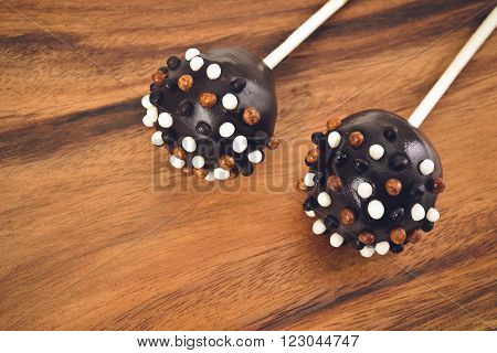 Cakepops in chocolate glaze on a wooden background