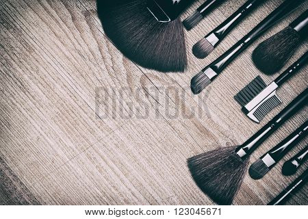 Set of various makeup brushes: for applying powder, eyeshadow, eyebrow brushes, fan brushes and others. Professional tools of makeup artist on shabby wooden surface. Copy space. Retro style processing