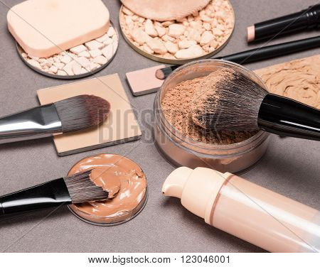 Basic makeup products to create the perfect complexion: liquid foundation, different types of powder, concealer pencil, correctors with brushes and cosmetic sponges on brown textured surface
