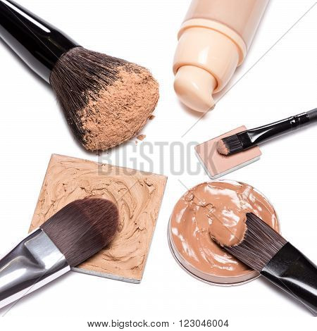 Basic makeup products to create beautiful skin tone and complexion. Corrector, foundation, powder with brushes on white background