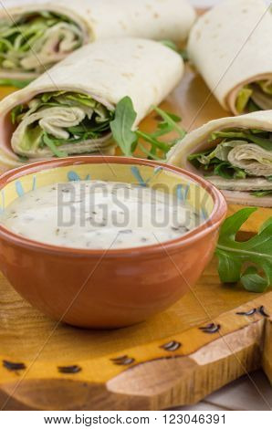 Cold wraps with ham iceberg lettuce and yogurt sauce on a rustic wooden cutting board