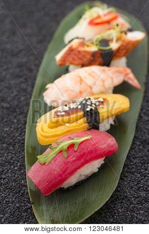 Sushi Nigiri Set On A Bamboo List And Black Sesame Background