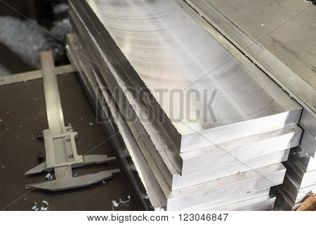 A stack of steel bars after milling. Measuring instruments calipers.