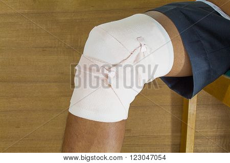 male is wrapping his knee injury with bandage.