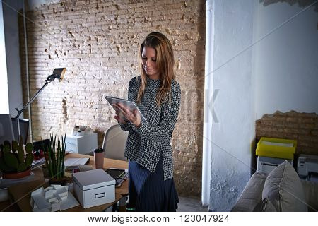 Businesswoman holding tablet pc at office standing and happy