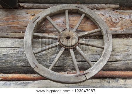 old vintage rural self-made wooden wheel at wall in ukrainian authentic village Kolochava