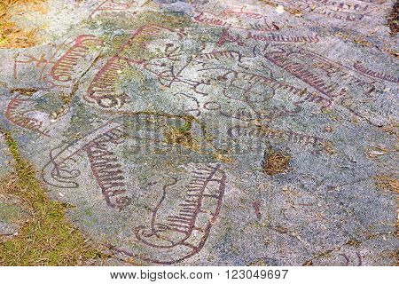 Very old rock carvings or petroglyphs dated from around 1000 BC found in nature close to Torhamn in Sweden. There are about 140 glyphs here. The glyphs have been painted to make them more visible.