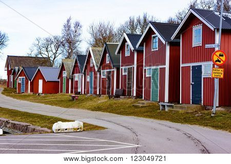 Torhamn Sweden - March 18 2016: The A row of red and white wooden fishing sheds along a small narrow road. These sheds are typical along the coast in southern Sweden.