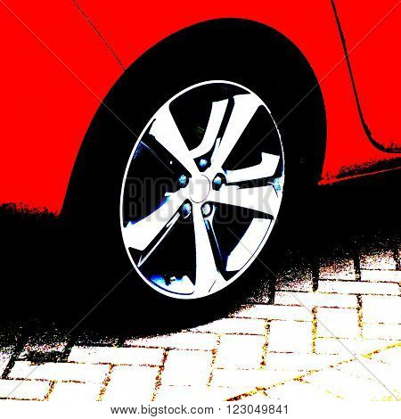 Wheel of a red car on a block paving driveway