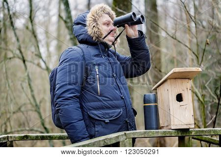 Ornithologist with binoculars and bird cage in the park on the bridge
