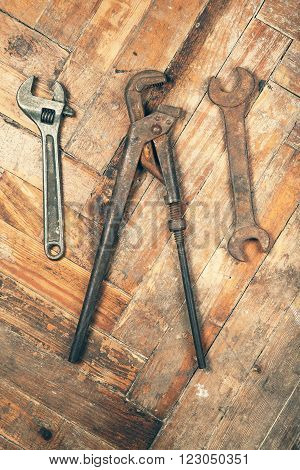 Set of old adjustable spanner, pipe wrench and open-end wrench on wooden floor