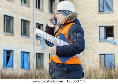 Building inspector talking on smartphone near the building