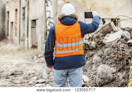 Building inspector filmed with tablet PC dilapidated building