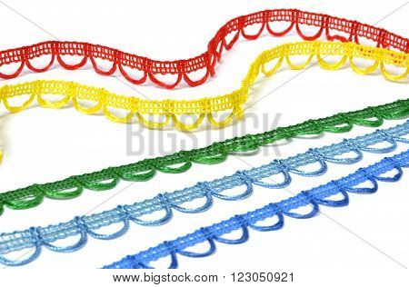 Curved strips of multicolored lace on white background