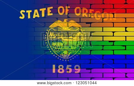 A well worn wall painted with a LGBT rainbow with the Oregon state flag