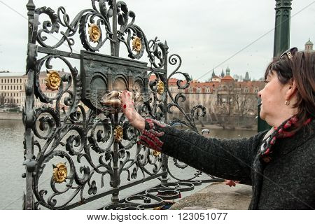 PRAGUE, CZECH REPUBLIC - FEBRUARY 13, 2016: An unidentified woman at the monument of St. John of Nepomuk on Charles Bridge