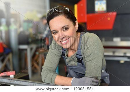 Portrait of successful metalworker woman in workshop