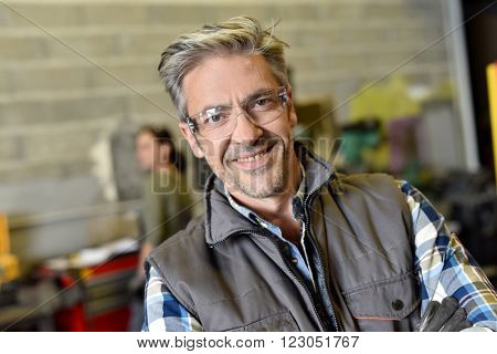 Portrait of middle-aged metalworker in workshop