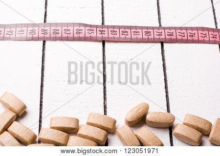 Pills and pink centimeter over the white background
