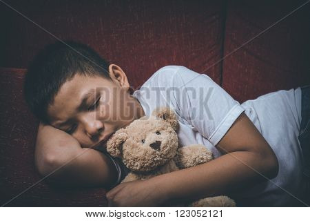Young Asian boy scared and alone, hugging his teddy