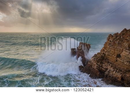 Ray of sunshine in the storm. Wave hitting the rocks in Sagres Portugal.
