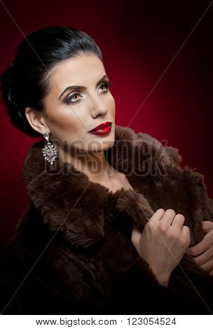 Attractive sexy young woman wearing a fur coat posing in studio on dark purple background. Portrait of sensual female with creative makeup, studio. Gorgeous eyes brunette lady with black fur collar