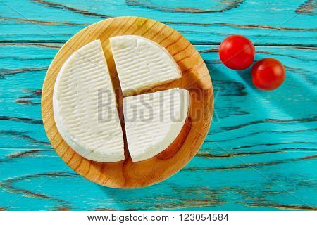 Tapas Burgos cheese on round board with cherry tomatoes Spain