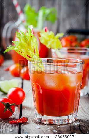 Cocktail Bloody Mary with ice in glasses on a wooden table