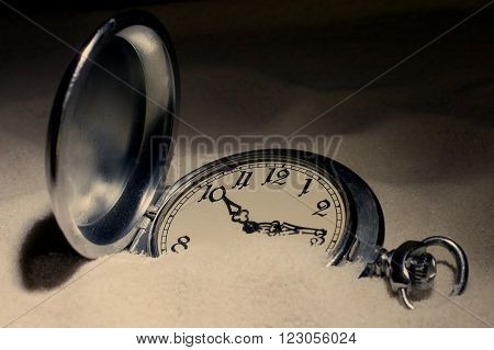 Antique pocket watch covered with sand (in the darkness) retro style