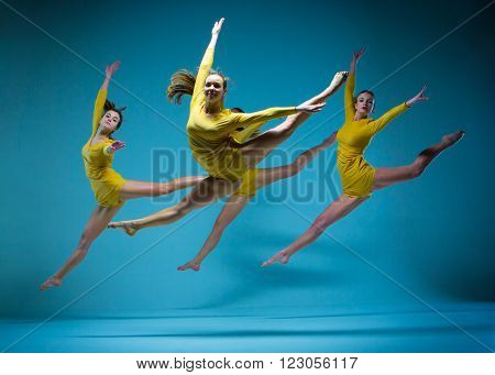The modern ballet dancers dancing on gray background