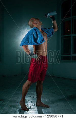 The young male athlete kickboxing on a black background with a towel after a workout