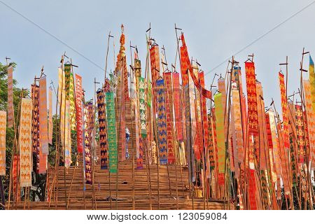 NORTHERN THAILAND - APRIL 14, 2011: Colorful multicolored flags and pennants adorn special bamboo tower.  Thai New Year - Songkran