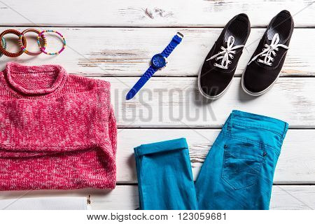 Pink sweatshirt with turquoise pants. Colorful outfit on white table. Bright clothing and black keds. Lady's outfit with fabric shoes.
