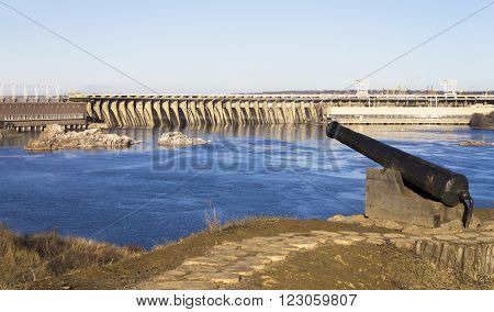 Ancient gun on a background of a dam and hydroelectric power plants. Bright, Contrast, Saturation picture. Symbolism.