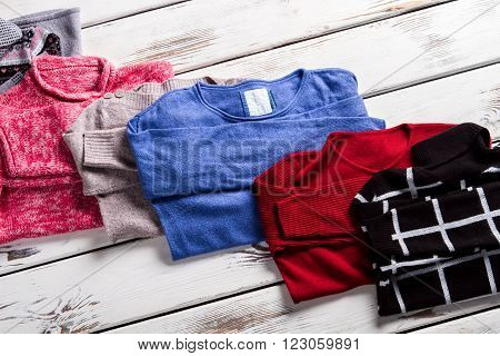 Bright and dark-colored sweaters. Sweaters on white wooden background. Warm clothing from fashion magazine. Few trendy sweaters.